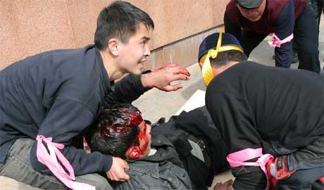 Demonstrantene tar hånd om en av sine egne som ble såret i dagens kamper i Bisjkek. (Foto: Scanpix / Reuters)
