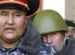 En soldat kikker frem bak ryggen til en politimann mens de holder vakt utenfor parlamentsbygget. (Foto: AP/Scanpix)