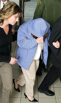 Et vitne dekker seg til i det hun ankommer rettssalen i Santa Barbara. Foto: Robyn Beck, AP Photo.