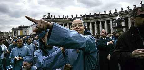 En nonne peker mot pipa med den svarte røyken etter den andre avstemningen tirsdag. Foto: Marco Longari, AFP.