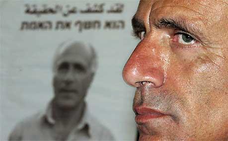 Mordechai Vanunu foran en plakat med hans bilde og den hebraiske teksten: «Han avslørte sannheten», 15. april 2005. Foto: AFP/ Gali Tibbon/ Scanpix