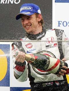Jenson Button sprutet champagne etter 3. plassen på Imola-banen. (Foto: AP/Scanpix)
