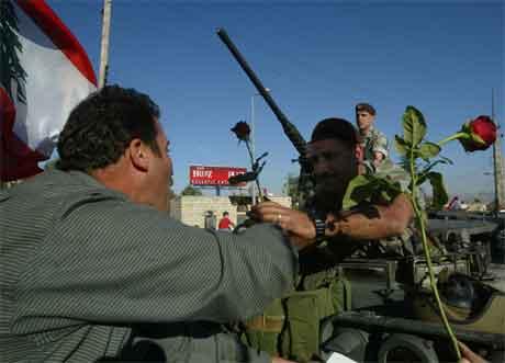 Ein mann gir blomar til ein libanesisk soldat som har innteke det tidlegare hovudkvarteret til den syriske etterretninga i Libanon. (Foto: AP/Scanpix)