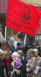 Et rødt flagg - men med bilde av Khodorkovskij, og i midten hans mor, Marina (Scanpix/AP)