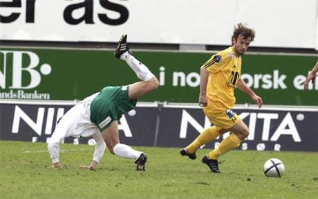 Ham-Kam-spiller går overende mens Bodø/Glimts Håvard Halvorsen er på vei framover. (Foto: Scnapix)
