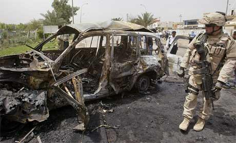 En amerikansk soldat ved en av bilene som eksploderte i Bagdad i dag. (Foto: Ali al-Saadi/AFP/Scanpix)