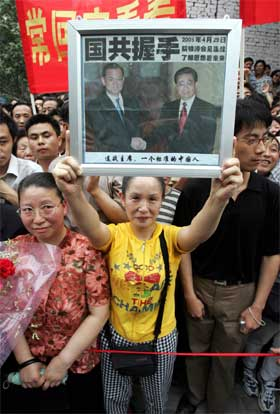 En kinesisk kvinne viser fram det historiske bildet av Kuomintang-lederen Lien Chans møte med Kinas president Hu Jintao. (Foto: AP/Scanpix)