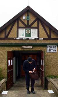 FERDIG STEMT: En mann forlater valglokalet i Gunnersbury i vest-London etter å ha avgitt sin stemme. (Foto: AFP)