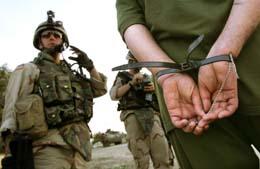 En USA-soldat med en irakisk fange. (Foto: C.Bouroncle, AFP)