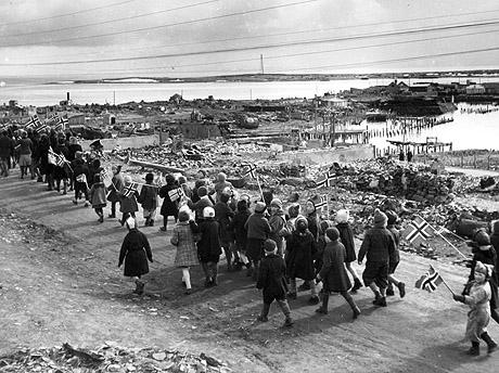 17. mai 1945 feires med barnetog i Vadsø. Ruiner av ødelagte bygninger i bakgrunnen. Foto: NTB / Scanpix