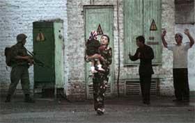 ANDISJAN: En kvinne bærer barnet sitt i sikkerhet etter at regjeringsstyrker gikk til angrep på folkemassene på torget i byen i går. (Foto: AP Photo/Efrem Lukatsky)