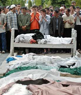 ANDISJAN: Innbyggerne i Andisjan begraver sine døde. Hvor mange som har blitt drept i urolighetene er umulig å si. Det kan være så mange som 500. (Foto: AFP PHOTO / DENIS SINYAKOV)