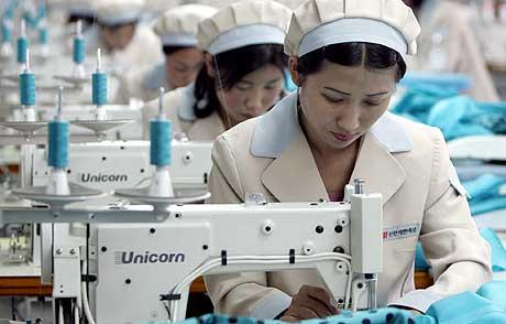PÅ RAD OG REKKE: Nordkoreanske arbeidere syr klær som skal selges i Sør-Korea. (Foto: Lee Jae-Won/AP)