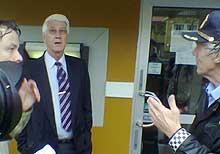 Banksjef Hans A Iversen diskuterer ranet utenfor Sparebanken Sørs filial på Fevik med politiet (foto: Børge Røssaak Nilsen)