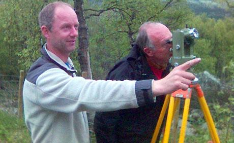 Jon Kvam (t.v) og geolog Erik Sloreby i Statens Vegvesen studerer steinblokka oppe i fjellsida.