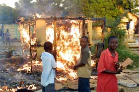Barn i Harare-forstaden Glen View ser en bod brenne ned etter myndighetenes aksjon. (Foto: AFP/Scanpix)