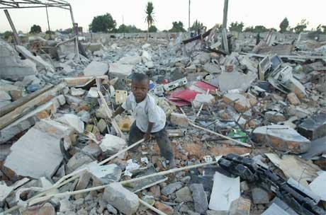 En gutt leter gjennom ruinene av nedrevne hus i Chitungwiza, 9 km sør for Harare. (Foto: AP/Scanpix)