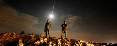 Israelske soldater overvåker unge landsmenn som etablerer den nye bosettingen Tal Yam etter at flere hus ble revet i Gush Katif søndag (Scanpix/AFP)
