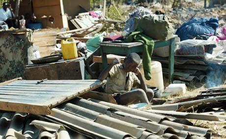 En tiåring passer på det som er igjen av familiens eiendeler etter at hjemmet hans på Porta Farm ble ødelagt torsdag. (Foto: AP)