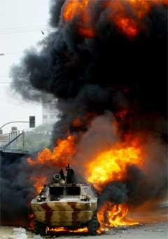 En palestinsk stridsvogn brenner etter å ha blitt satt fyr på i sammenstøtet i Gaza i dag. (Foto: Scanpix/AP/H. Moussa)