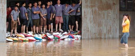 """Ansatte i et varhus i Fuzhou har barrikadert seg mot flommen fra """"Haitang"""". (Foto: AP)"""