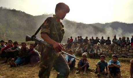 Maoistisk soldat går inn i landsby med barn. Nepal er et av de mange land der barn blir soldater, påpeker Amnesty og FN (Scanpix/AP)