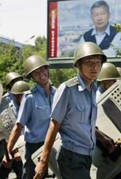 Soldater marsjerer foran et bilde av Bakijev mens han ennå er presidentkandidat (Scanpix/AFP)