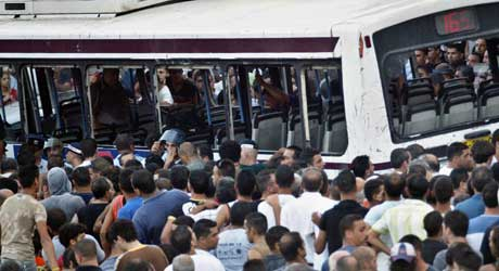 En stor flokk arabere omringet bussen, og noen kastet også stein og flasker mot den (Scanpix/Reuters)