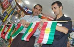 Noen menn gjør klar bannere med kurdiske flagg til åpningen av den kurdiske nasjonalforsamlingen. (Foto: Scanpix/AFP. S. Hamed)