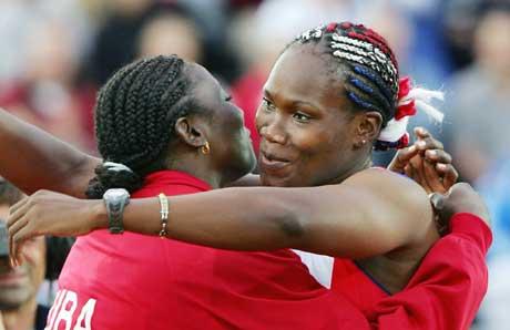 Osleidys Menendez (t.h.) får en klem av lagvenninde Sonia Bisset etter verdensrekorden. (Foto: AFP/Scanpix)