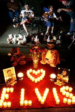Tilreisene til Memphis som sitter ved sin hyllest til Elvis Presley. Foto: Carlo Allegri, AFP Photo / Scanpix.