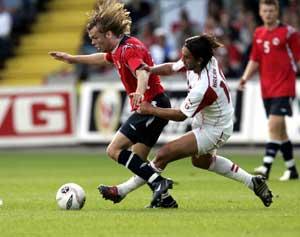 """Christian Grindhreim ( til venstre) blir """" tatt hånd om"""" av en motspiller under onsdagens privatlandskamp mellom Norge og Sveits på Ullevaal Stadion. I bakgrunnen John Arne Riise. (Foto: Tor Richardsen / SCANPIX)"""