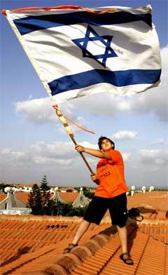 Ein ung aktivist viftar med det israelske flagget på eit hustak i Neve Dekalim. (Foto: AFP/Scanpix)