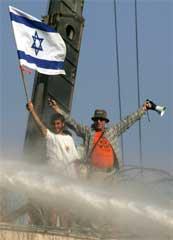 To menn står på taket av synagogen mens det spyles med vannkanoner fra bakken. (Foto: Scanpix/AP/E. Morenatti)