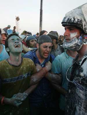 Jødiske bosettere synger religiøse sanger foran politimenn som fikk syre, sand og grønn væske kastet på seg. (Foto: Scanpix / AP)