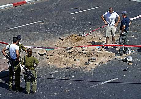 Israelske soldater inspiserer krateret etter en av rakettene som ble skutt mot Eilat.(Foto:AFP/Scanpix)