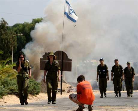 En ung jødisk bosetter venter langs veien mens israelske soldater går inn i bosettingen Katif i dag. (Foto:REUTERS/Paul Hanna )