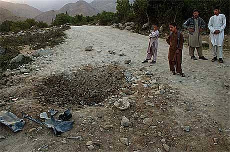 Afghanistan er en eneste stor krigskirkegård. To afghanske gutter betrakter et krater etter en rakett.(Foto:AP/Scanpix)