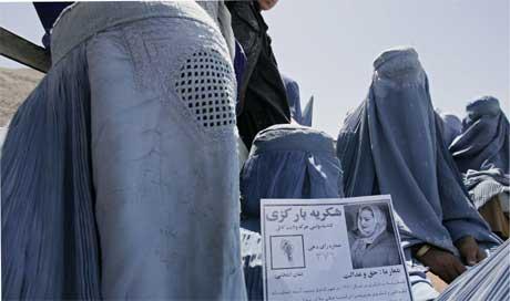 Afghansk kvinne med pamflett for en kvinnelig valgkandidat (Scanpix/Reuters)