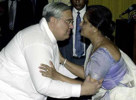 På dette bildet gir Chandrika Kumaratunga broren Anura Bandaranaike en klem etter at han var tatt i ed som turistminister (Scanpix/Reuters)