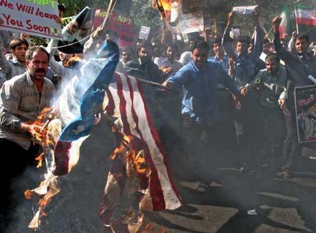 Under de kraftige protestene brente demonstrantene det amerikanske og franske flagget (Scanpix/AP)