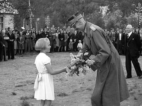 Kong Haakon besøker Melbu for å se på gjenreisningen av byen etter 2. verdenskrig. Her får kongen blomster av en liten jente. Foto: NTB arkiv / Scanpix