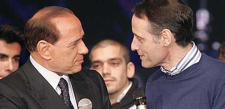 Italias statsminister Silvio Berlusconi, til venstre i bildet, hilser på den avtroppende kommissæren for Italias Røde Kors, Maurizio Scelli, i mars i år. (Foto: AP/Scanpix)