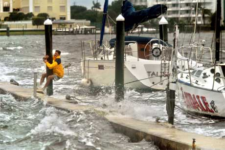 Ein mann klamrar seg fast til ein stolpe på båthamna i Palm Beach. (Foto: AP/Scanpix)