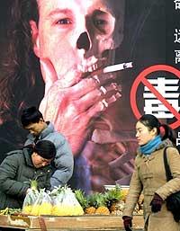 En fruktselger foran en anti-røykeplakat i Beijing i mars i år. (Foto: AFP/Scanpix)