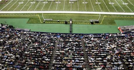 Folk sitter på tribunene mens de venter på at uværet skal gi seg. (Foto: Scanpix / AP)
