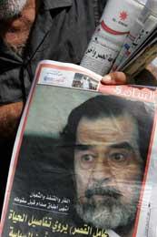 Avisselger med bilde av Saddam, som blir stilt for retten 19.oktober (Scanpix/AFP)