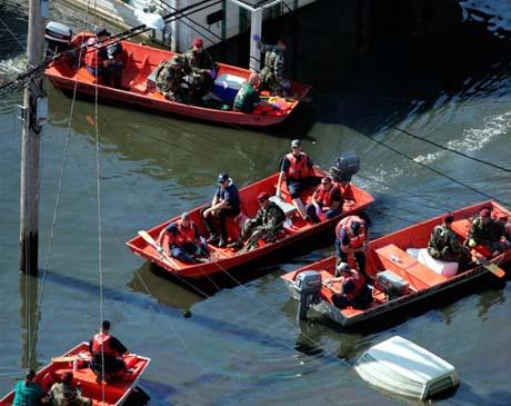 Redningsmannskaper og soldater går - eller ror - fra hus til hus i New Orleans. (Foto: D.Phillip, Reuters)
