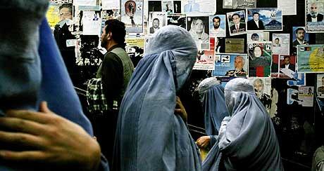 Afghanske kvinner spaserer forbi valgplakater i Kabul. Om en uke er det valg i Afghanistan. (Foto: AP/Scanpix)
