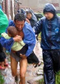 En innbygger blir evakuert fra hjemmet sitt i byen Taizhou i Zhejiang-provinsen. (Foto: Reuters/Scanpix)